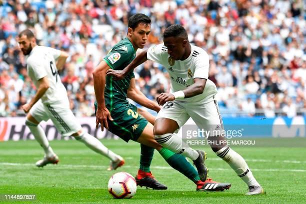 TOPSHOT Real Madrid's Brazilian forward Vinicius Junior challenges Real Betis' Algerian defender Aissa Mandi during the Spanish League football match...