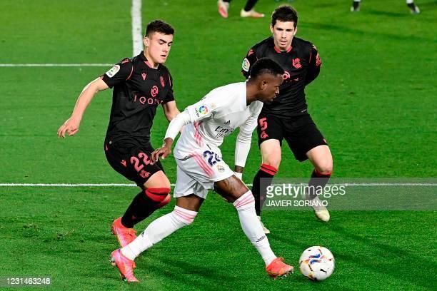 Real Madrid's Brazilian forward Vinicius Junior challenges Real Sociedad's Spanish forward Ander Barrenetxea and Real Sociedad's Spanish midfielder...