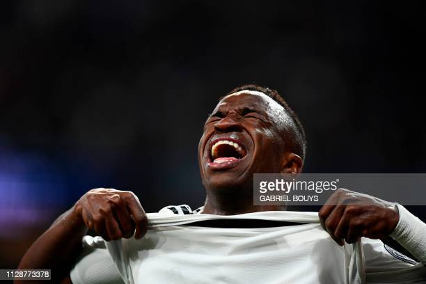 Real Madrid's Brazilian forward Vinicius Junior reacts as he walks off the pitch after getting injured during the UEFA Champions League round of 16...