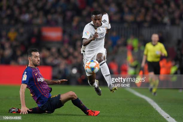 Real Madrid's Brazilian forward Vinicius Junior vies for the ball with Barcelona's Spanish midfielder Sergio Busquets during the Spanish Copa del Rey...