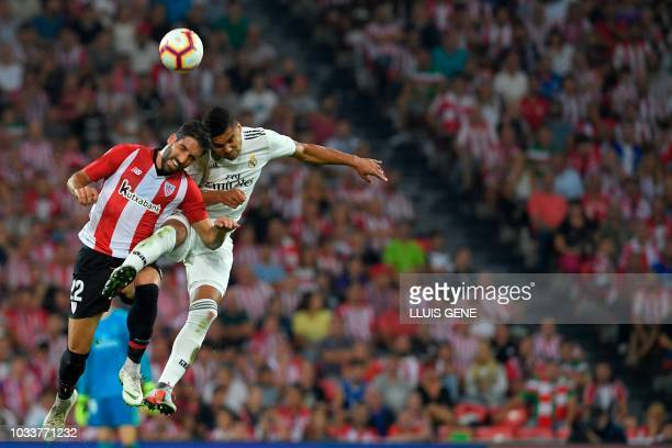 Real Madrid's Brazilian midfielder Casemiro and Athletic Bilbao's Spanish midfielder Raul Garcia jump for the ball during the Spanish league football...