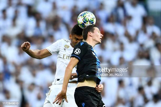 Real Madrid's Brazilian midfielder Casemiro and Club Brugge's Belgian midfielder Hans Vanaken jump for the ball during the UEFA Champions league...