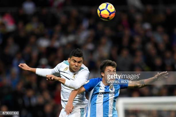 Real Madrid's Brazilian midfielder Casemiro and Malaga's Venezuelan forward Adalberto Penaranda jump for the ball during the Spanish league football...