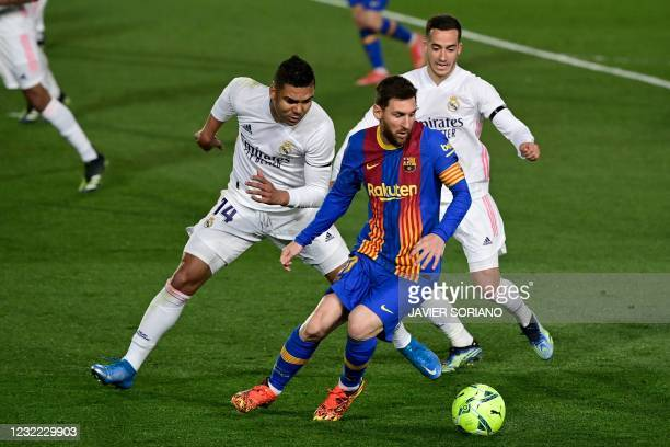 Real Madrid's Brazilian midfielder Casemiro and Real Madrid's Spanish forward Lucas Vazquez challenge Barcelona's Argentinian forward Lionel Messi...