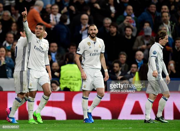 Real Madrid's Brazilian midfielder Casemiro celebrates a goal with Real Madrid's French forward Karim Benzema and Real Madrid's Croatian midfielder...