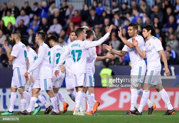 Real Madrid's Brazilian midfielder Casemiro celebrates a goal with teammates during the Spanish league footbal match between Malaga CF and Real...