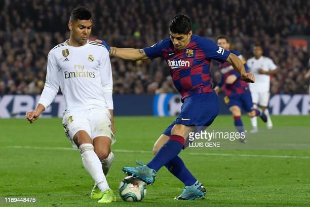 "Real Madrid's Brazilian midfielder Casemiro challenges Barcelona's Uruguayan forward Luis Suarez during the ""El Clasico"" Spanish League football..."
