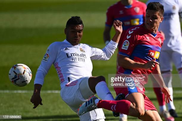 Real Madrid's Brazilian midfielder Casemiro challenges Elche's Argentinian forward Guido Carrillo during the Spanish League football match between...