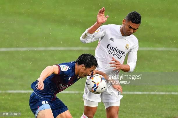Real Madrid's Brazilian midfielder Casemiro challenges Huesca's Japanese forward Shinji Okazaki during the Spanish league football match between SD...