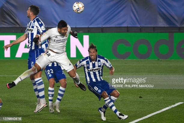 Real Madrid's Brazilian midfielder Casemiro heads the ball beside Alaves' Spanish midfielder Tomas Pina during the Spanish League football match...