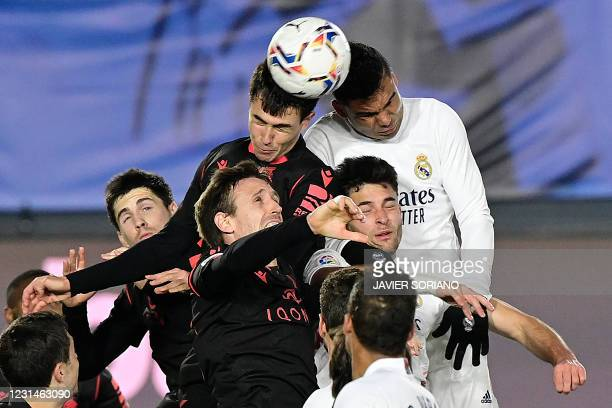 Real Madrid's Brazilian midfielder Casemiro heads the ball with Real Sociedad's Spanish midfielder Martin Zubimendi during the Spanish league...