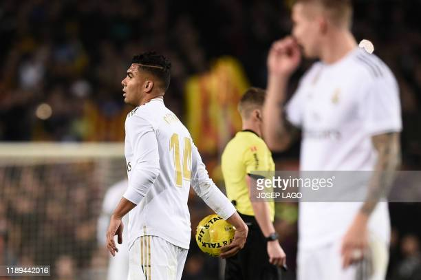 Real Madrid's Brazilian midfielder Casemiro holds a ball thrown by Barcelona's supporters on the pitch during the El Clasico Spanish League football...