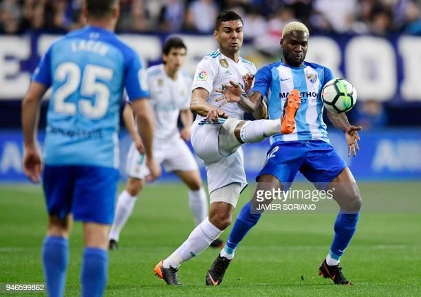 Real Madrid's Brazilian midfielder Casemiro vies with Malaga's Nigerian forward Brown Ideye during the Spanish league footbal match between Malaga CF...