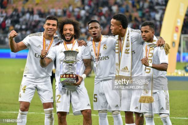 Real Madrid's Brazilian players Casemiro Marcelo Vinicius Junior Eder Militao and Rodrygo pose with the trophy after winning the Spanish Super Cup...