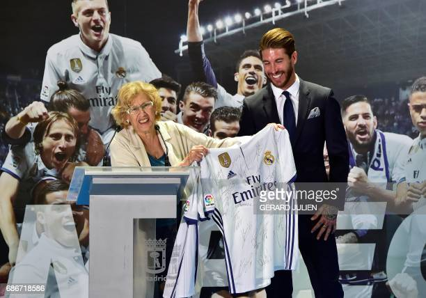 Real Madrid's captain and defender, Sergio Ramos presents a team jersey to a Mayor of Madrid Manuela Carmena at the Madrid Town hall on Plaza Cibeles...
