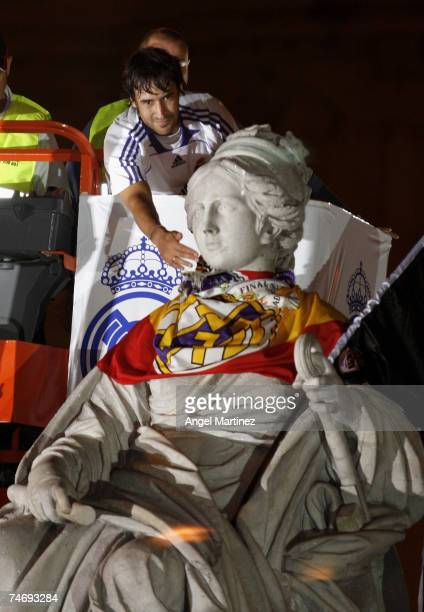 Real Madrid's captain Raul Gonzalez places a Spanish flag on the Cibeles fountain in Madrid during a victory parade after winning the Spanish league...