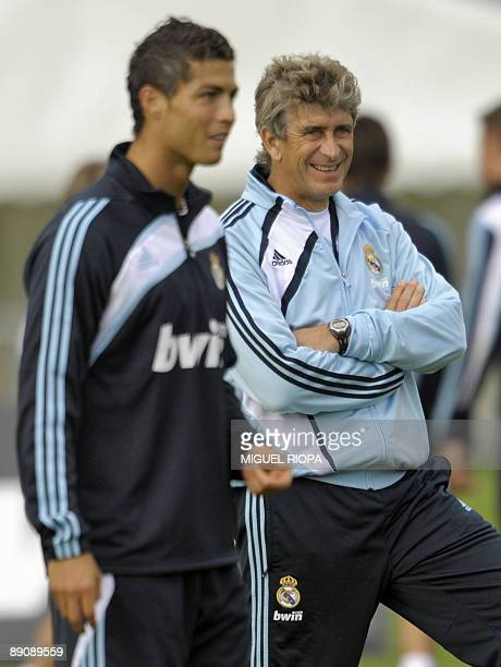 Real Madrid's Chilean coach Manuel Pellegrini smiles next to Portuguese striker Cristiano Ronaldo during their second training session on July 18...