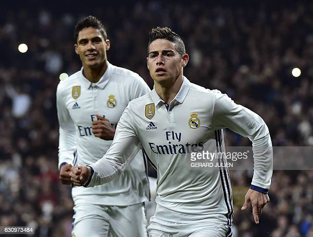 Real Madrid's Colombian midfielder James Rodriguez celebrates past Real Madrid's French defender Raphael Varane after scoring on a penalty kick...