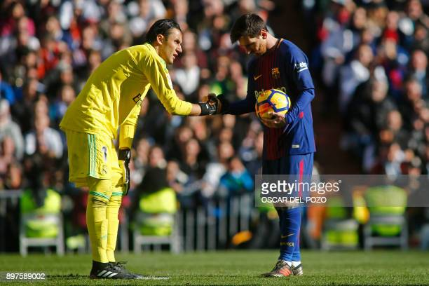 Real Madrid's Costa Rican goalkeeper Keylor Navas and Barcelona's Argentinian forward Lionel Messi prepare for a penalty kick during the Spanish...