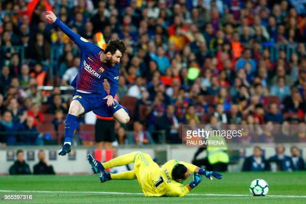 TOPSHOT Real Madrid's Costa Rican goalkeeper Keylor Navas blocks a shot on goal by Barcelona's Argentinian forward Lionel Messi during the Spanish...