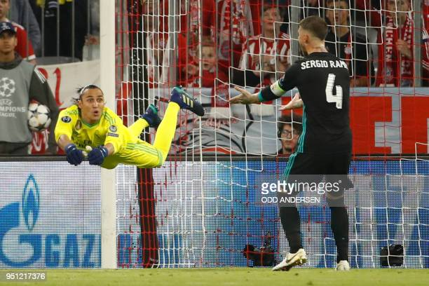 Real Madrid's Costa Rican goalkeeper Keylor Navas dives for the ball next to Real Madrid's Spanish defender Sergio Ramos during the UEFA Champions...