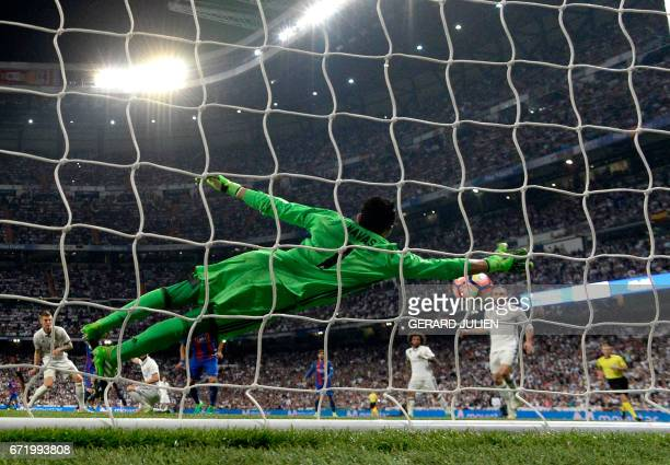 Real Madrid's Costa Rican goalkeeper Keylor Navas dives to unsuccesfully stop a goal by Barcelona's Argentinian forward Lionel Messi during the...