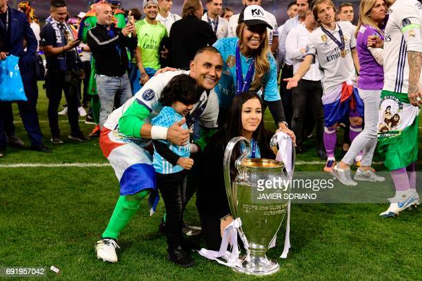 Real Madrid's Costa Rican goalkeeper Keylor Navas his wife Andrea Salas and children Daniela and Mateo pose with the trophy after Real Madrid won the...