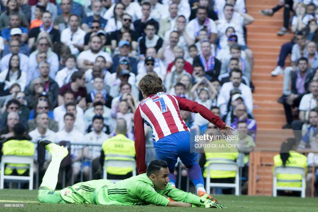 Real Madrid's Costa Rican goalkeeper Keylor Navas (DOWN) lies on the field after Atletico Madrid's French forward Antoine Griezmann (C) scored a goal during the Spanish league football match Real Madrid CF vs Club Atletico de Madrid at the Santiago Bernabeu stadium in Madrid on April, 8, 2017. /