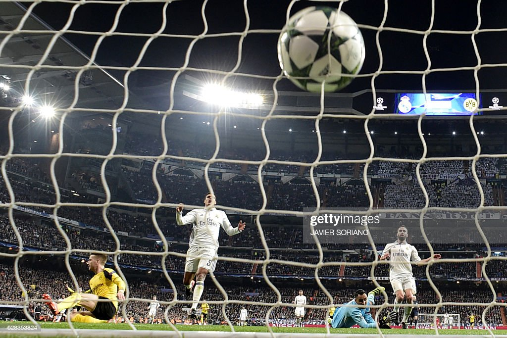 Real Madrid's Costa Rican goalkeeper Keylor Navas (2ndR) looks at the ball after Dortmund's midfielder Marco Reus' goal (L) during the UEFA Champions League football match Real Madrid CF vs Borussia Dortmund at the Santiago Bernabeu stadium in Madrid on December 7, 2016. / AFP / JAVIER