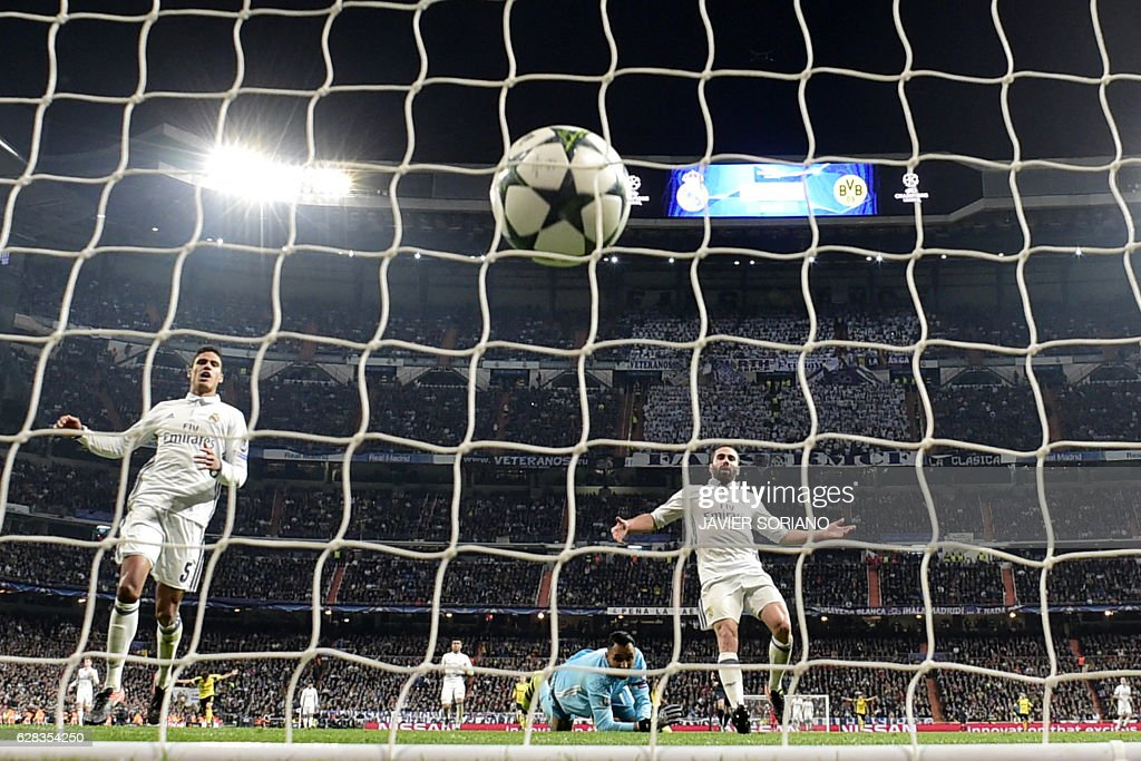 Real Madrid's Costa Rican goalkeeper Keylor Navas (C), Real Madrid's French defender Raphael Varane (L) and Real Madrid's defender Dani Carvajal gesture after Dortmund's goal during the UEFA Champions League football match Real Madrid CF vs Borussia Dortmund at the Santiago Bernabeu stadium in Madrid on December 7, 2016. / AFP / JAVIER