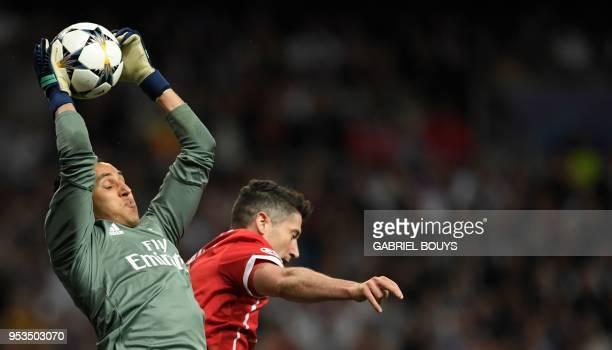 Real Madrid's Costa Rican goalkeeper Keylor Navas saves the ball in front of Bayern Munich's Polish forward Robert Lewandowski during the UEFA...