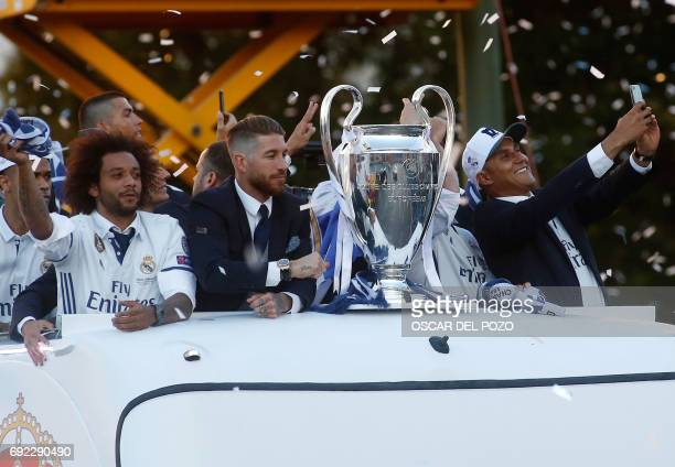 Real Madrid's Costa Rican goalkeeper Keylor Navas takes a selfie photo with the trophy as he celebrates the team's win with Real Madrid's defender...