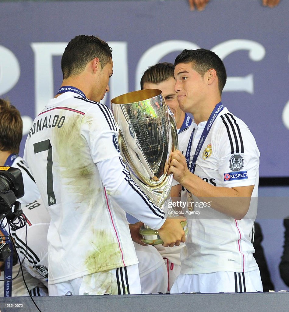 Real Madrid's Cristiano Ronaldo (L), Gareth Bale (C) and James Rodriges (R) celebrate with the UEFA Super Cup after winning the UEFA Super Cup football match between Real Madrid and FC Sevilla on August 12, 2014 at Cardiff City Stadium in Cardiff, Wales on August 12, 2014.