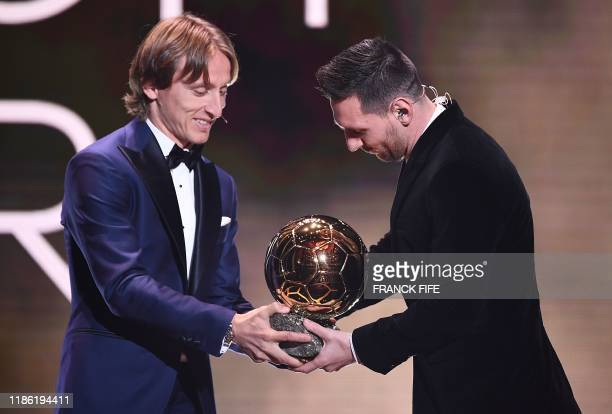 Real Madrid's Croatian midfielder and last year's Ballon d'Or winner Luka Modric gives his trophy to Barcelona's Argentinian forward Lionel Messi...