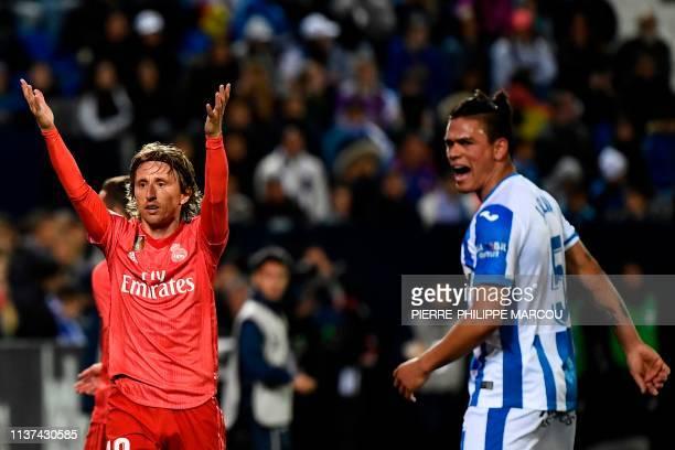 Real Madrid's Croatian midfielder Luka Modric and Leganes' Argentinian defender Jonathan Silva react during the Spanish league football match between...