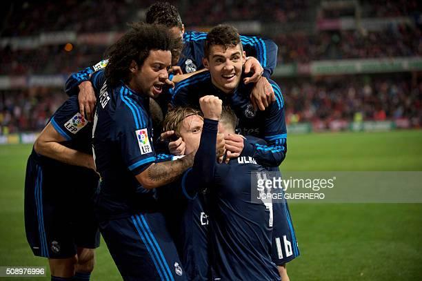 Real Madrid's Croatian midfielder Luka Modric celebrates a goal with teammates during the Spanish league football match Granada FC vs Real Madrid CF...