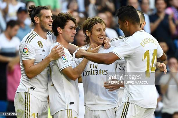 Real Madrid's Croatian midfielder Luka Modric celebrates with teammates scoring his team's third goal during the Spanish league football match...