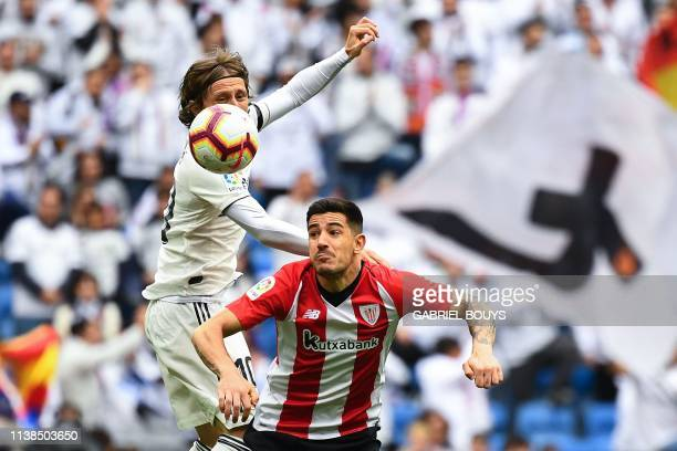 Real Madrid's Croatian midfielder Luka Modric challenges Athletic Bilbao's Spanish defender Yuri Berchiche during the Spanish League football match...