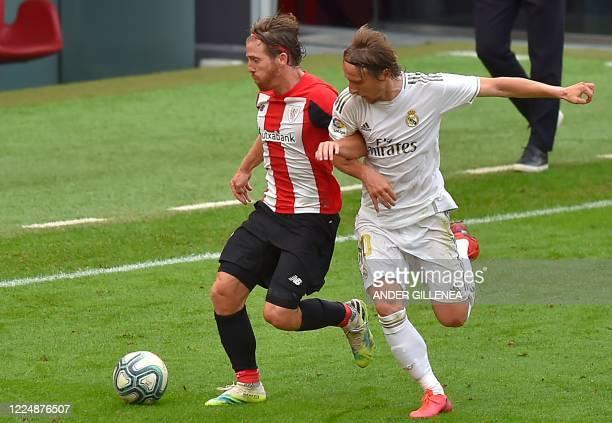 Real Madrid's Croatian midfielder Luka Modric challenges Athletic Bilbao's Spanish forward Iker Muniain during the Spanish League football match...