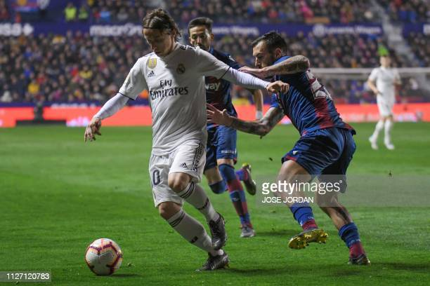 Real Madrid's Croatian midfielder Luka Modric challenges Levante's Spanish defender Antonio Luna during the Spanish league football match between...