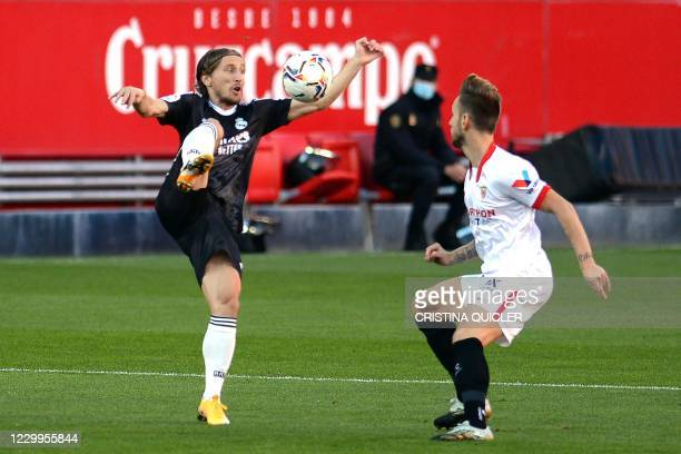 Real Madrid's Croatian midfielder Luka Modric challenges Sevilla's Croatian midfielder Ivan Rakitic during the Spanish League football match between...