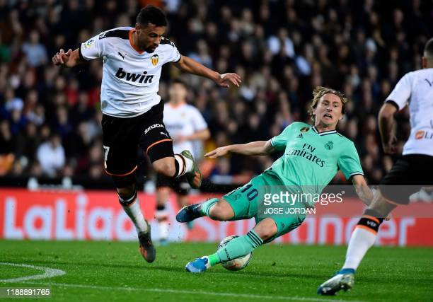 Real Madrid's Croatian midfielder Luka Modric falls as he vies with Valencia's French midfielder Francis Coquelin during the Spanish League football...
