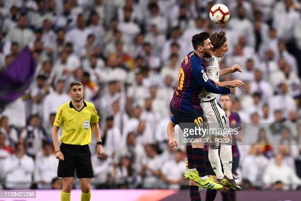 TOPSHOT Real Madrid's Croatian midfielder Luka Modric jumps for the ball with Barcelona's Argentinian forward Lionel Messi during the Spanish league...