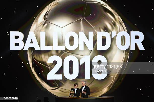Real Madrid's Croatian midfielder Luka Modric listens to Former French footballer and host David Ginola after receiving the 2018 Men's Ballon d'Or...