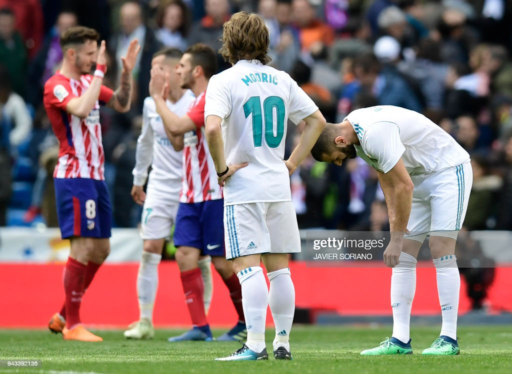 Real Madrid's Croatian midfielder Luka Modric looks at Atletico players celebrating their victory at the end of the Spanish league football match between Real Madrid CF and Club Atletico de Madrid at the Santiago Bernabeu stadium in Madrid on April 8, 2018. /