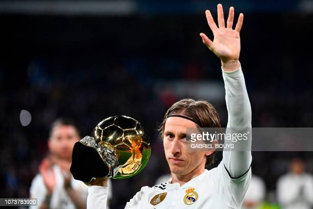 Real Madrid's Croatian midfielder Luka Modric poses with his Ballon d'Or trophy before the Spanish League football match between Real Madrid and Rayo...