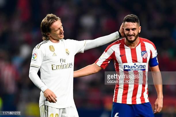 TOPSHOT Real Madrid's Croatian midfielder Luka Modric speaks to Atletico Madrid's Spanish midfielder Koke at the end of the Spanish league football...
