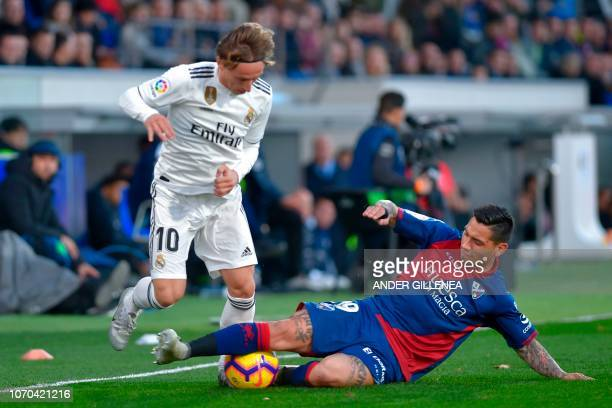 Real Madrid's Croatian midfielder Luka Modric vies for the ball with Huesca's Argentinian forward Chimy avila during the Spanish league football...