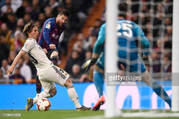 Real Madrid's Croatian midfielder Luka Modric vies with Barcelona's Argentinian forward Lionel Messi during the Spanish league football match between...