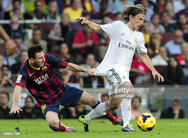 Real Madrid's Croatian midfielder Luka Modric vies with Barcelona's Argentinian forward Lionel Messi during the Spanish league Clasico football match...